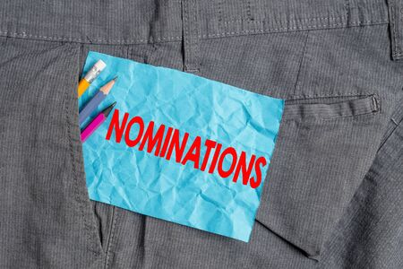 Text sign showing Nominations. Business photo showcasing the act of officially suggesting someone for a job or position Writing equipment and blue note paper inside pocket of man work trousers 스톡 콘텐츠