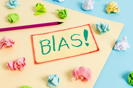 Writing note showing Bias. Business concept for inclination or prejudice for or against one demonstrating group Colored crumpled papers empty reminder blue yellow clothespin