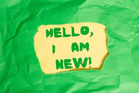 Writing note showing Hello I Am New. Business concept for used as greeting or to begin telephone conversation Green crumpled colored paper sheet torn colorful background