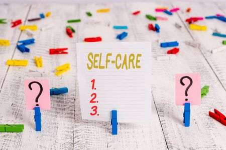 Text sign showing Self Care. Business photo showcasing practice of taking action preserve or improve ones own health Scribbled and crumbling sheet with paper clips placed on the wooden table