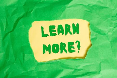 Writing note showing Learn More question. Business concept for gain knowledge or skill studying practicing Green crumpled colored paper sheet torn colorful background