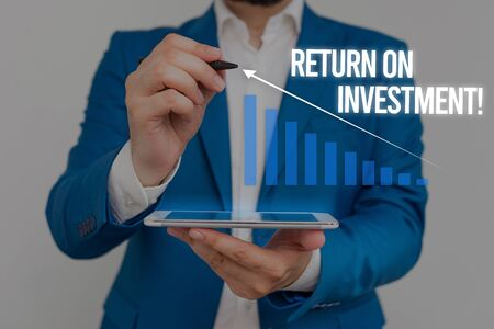 Conceptual hand writing showing Return On Investment. Concept meaning perforanalysisce measure used evaluate efficiency of investment Male wear formal suit presenting presentation smart device