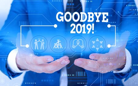 Conceptual hand writing showing Goodbye 2019. Concept meaning express good wishes when parting or at the end of last year Male wear formal suit presenting presentation smart device Stock Photo
