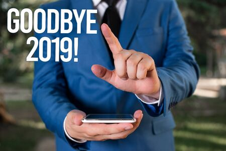 Text sign showing Goodbye 2019. Business photo showcasing express good wishes when parting or at the end of last year Man with opened hands stands in suite. Concept with copy space and man