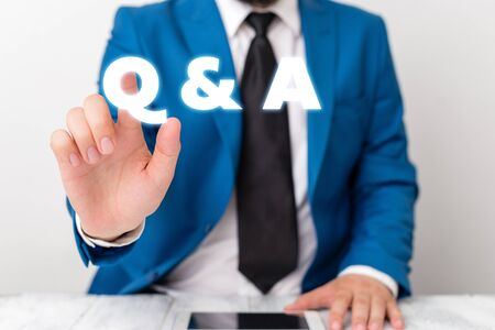 Handwriting text writing Q And A. Conceptual photo defined as questions being asked and answers Businessman with pointing finger in front of him Stock fotó - 129481984