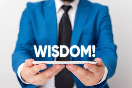 Handwriting text writing Wisdom. Conceptual photo quality having experience knowledge and good judgement something Businessman in blue suite with a tie holds lap top in hands 写真素材