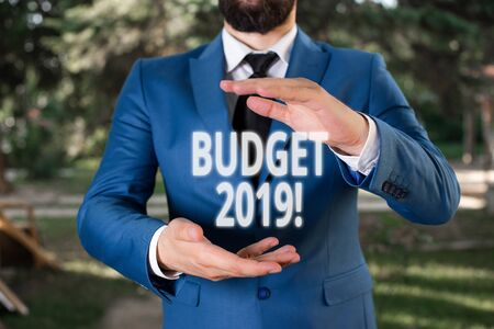 Handwriting text Budget 2019. Conceptual photo the estimate of income and expenditure for current year Man with opened hands stands in suite. Concept with copy space and man