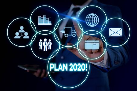 Text sign showing Plan 2020. Business photo showcasing detailed proposal doing achieving something next year Male human wear formal work suit presenting presentation using smart device 版權商用圖片