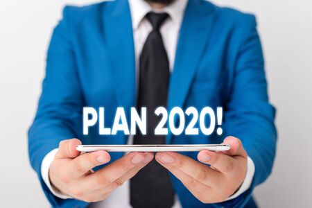 Handwriting text writing Plan 2020. Conceptual photo detailed proposal doing achieving something next year Businessman in blue suite with a tie holds lap top in hands 版權商用圖片