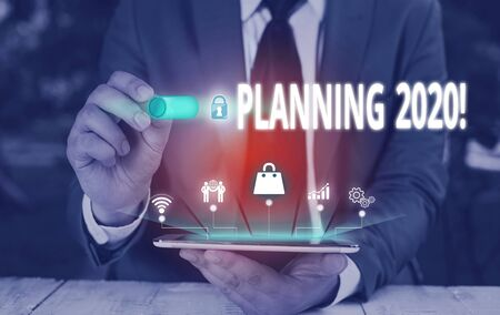Writing note showing Planning 2020. Business concept for process of making plans for something next year Male wear formal suit presenting presentation smart device