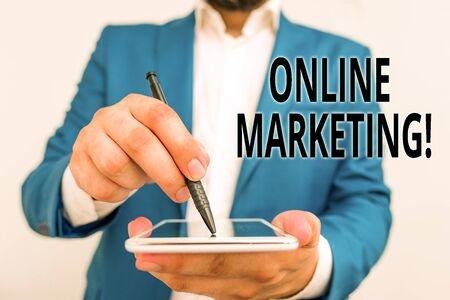 Conceptual hand writing showing Online Marketing. Concept meaning leveraging web based channels spread about companys brand Businessman in blue suite with laptop pointing with finger 写真素材