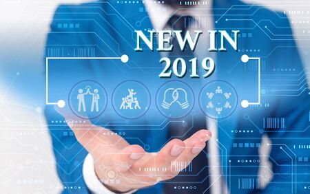 Writing note showing New In 2019. Business concept for what will be expecting or new creation for the year 2019 Male wear formal work suit presenting presentation smart device 写真素材