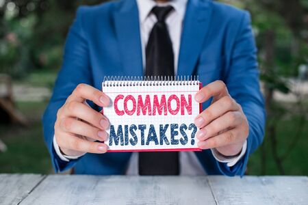 Word writing text Common Mistakes Question. Business photo showcasing repeat act or judgement misguided making something wrong Man holds empty paper with copy space in front of him