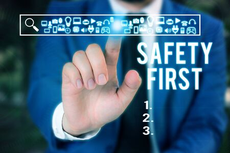 Word writing text Safety First. Business photo showcasing used to say that the most important thing is to be safe Male human wear formal work suit presenting presentation using smart device