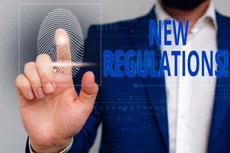 Text sign showing New Regulations. Business photo showcasing rules made government order control something done Male human wear formal work suit presenting presentation using smart device Archivio Fotografico