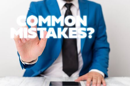 Handwriting text writing Common Mistakes question. Conceptual photo repeat act or judgement misguided or wrong Businessman with pointing finger in front of him Stockfoto