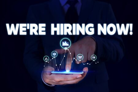 Writing note showing We Re Hiring Now. Business concept for recently employ someone or pay someone to do particular job Male wear formal suit presenting presentation smart device Banque d'images - 129642056