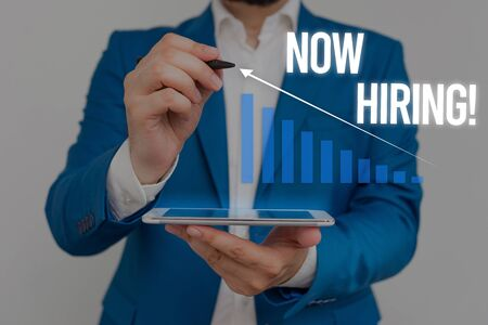 Conceptual hand writing showing Now Hiring. Concept meaning finding evaluating working relationship with future employees Male wear formal suit presenting presentation smart device Banque d'images - 129642059