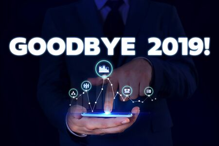 Writing note showing Goodbye 2019. Business concept for express good wishes when parting or at the end of last year Male wear formal suit presenting presentation smart device 스톡 콘텐츠