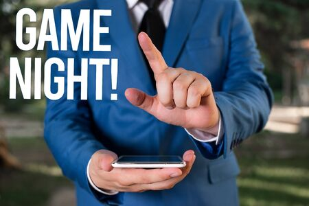 Text sign showing Game Night. Business photo showcasing usually its called on adult play dates like poker with friends Man with opened hands stands in suite. Concept with copy space and man