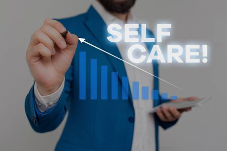 Writing note showing Self Care. Business concept for practice of taking action preserve or improve ones own health Male wear formal work suit presenting presentation smart device