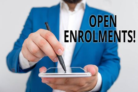 Conceptual hand writing showing Open Enrolments. Concept meaning when employees may make changes to elected fringe benefit Businessman in blue suite with laptop pointing with finger