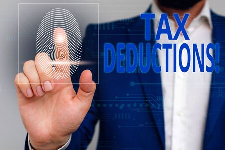Text sign showing Tax Deductions. Business photo showcasing reduction income that is able to be taxed of expenses Male human wear formal work suit presenting presentation using smart device Stock Photo