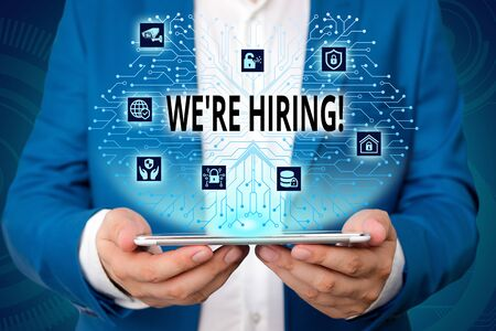 Handwriting text writing We Are Re Hiring. Conceptual photo process of reviewing applications and finding candidates Male human wear formal work suit presenting presentation using smart device Banque d'images - 129642668