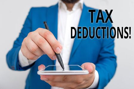 Conceptual hand writing showing Tax Deductions. Concept meaning reduction income that is able to be taxed of expenses Businessman in blue suite with laptop pointing with finger Stock Photo