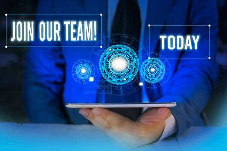 Word writing text Join Our Team. Business photo showcasing invite someone to work together for particular purpose target Male human wear formal work suit presenting presentation using smart device Banque d'images - 129642768