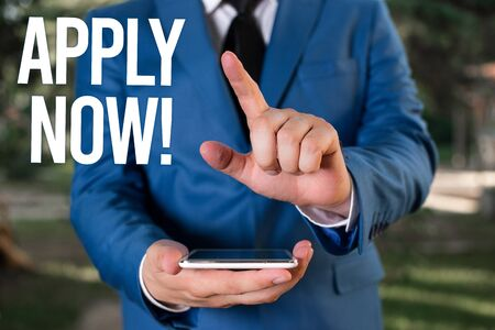 Text sign showing Apply Now. Business photo showcasing request something officially in writing or by sending in form Man with opened hands stands in suite. Concept with copy space and man