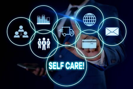 Text sign showing Self Care. Business photo showcasing practice of taking action to preserve or improve ones own health Male human wear formal work suit presenting presentation using smart device Stockfoto