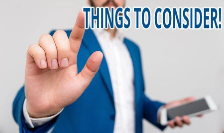 Conceptual hand writing showing Things To Consider. Concept meaning think about something carefully in order to make decision Businessman pointing with pen in empty copy space Stok Fotoğraf - 129360425