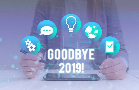 Conceptual hand writing showing Goodbye 2019. Concept meaning express good wishes when parting or at the end of last year Female human wear formal work suit presenting smart device Stock Photo