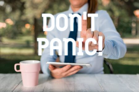 Text sign showing Don T Panic. Business photo text suddenly feel so worried or frightened that you can not behave Female business person sitting by table and holding mobile phone