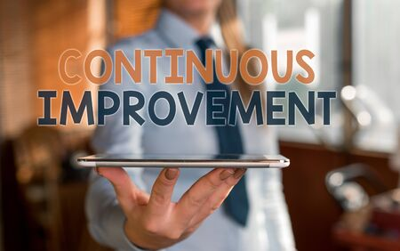 Writing note showing Continuous Improvement. Business concept for ongoing effort to improve products or processes Blurred woman in the background pointing with finger in empty space