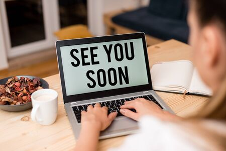 Handwriting text See You Soon. Conceptual photo used for saying goodbye to someone and going to meet again soon woman laptop computer smartphone mug office supplies technological devices Stok Fotoğraf