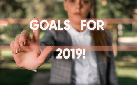 Word writing text Goals For 2019. Business photo showcasing object of demonstratings ambition or effort aim or desired result Business woman in the nature pointing with the finger into empty space