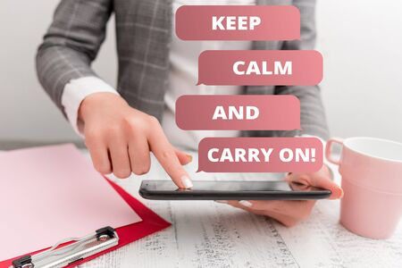 Text sign showing Keep Calm And Carry On. Business photo text slogan calling for persistence face of challenge Business concept with mobile phone in the hand Reklamní fotografie