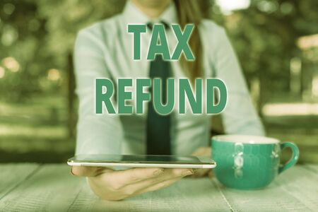 Handwriting text Tax Refund. Conceptual photo refund on tax when the tax liability is less than the tax paid Business woman sitting by the table with cup of coffee and mobile phone Stock Photo