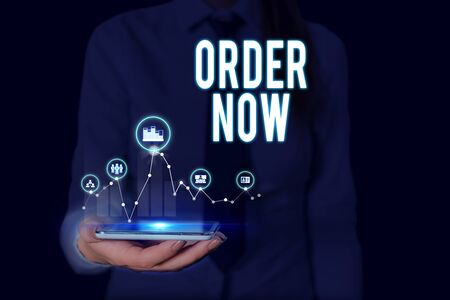 Text sign showing Order Now. Business photo text the activity of asking for goods or services from a company Woman wear formal work suit presenting presentation using smart device Stock Photo