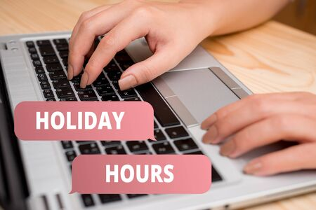 Handwriting text writing Holiday Hours. Conceptual photo employee receives twice their normal pay for all hours woman laptop computer smartphone mug office supplies technological devices Фото со стока