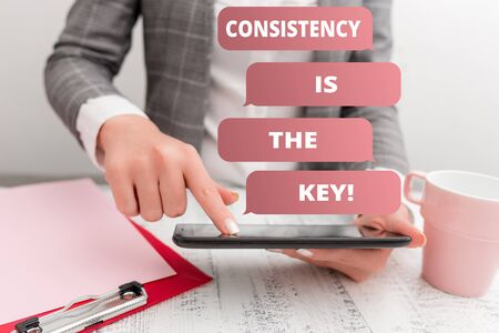 Text sign showing Consistency Is The Key. Business photo text by Breaking Bad Habits and Forming Good Ones Business concept with mobile phone in the hand