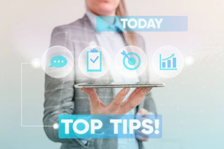 Writing note showing Top Tips. Business concept for small but particularly useful piece of practical advice Female human wear formal work suit presenting smart device