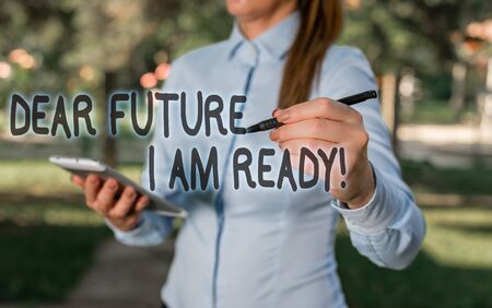 Conceptual hand writing showing Dear Future I Am Ready. Concept meaning suitable state for action or situation being fully prepared Woman in a blue shirt pointing with her finger into empty space