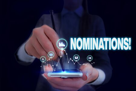 Writing note showing Nominations. Business concept for action of nominating or state being nominated for prize Woman wear formal work suit presenting presentation using smart device Imagens