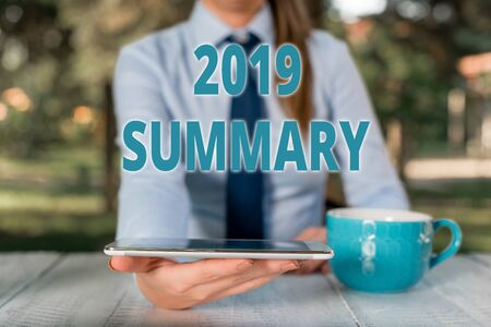 Handwriting text 2019 Summary. Conceptual photo brief comprehensive especially covering the main points of 2019 Business woman sitting by the table with cup of coffee and mobile phone