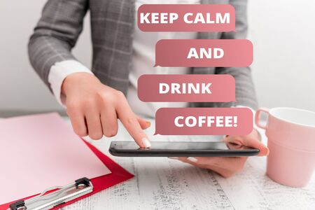 Text sign showing Keep Calm And Drink Coffee. Business photo text encourage demonstrating to enjoy caffeine drink and relax Business concept with mobile phone in the hand Banco de Imagens