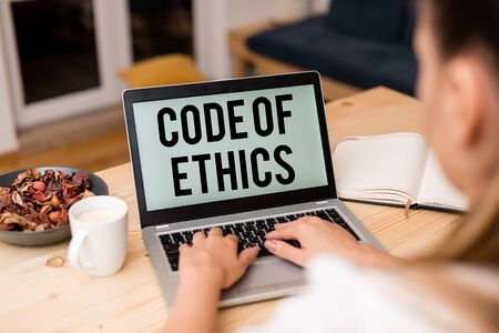 Handwriting text Code Of Ethics. Conceptual photo basic guide for professional conduct and imposes duties woman laptop computer smartphone mug office supplies technological devices