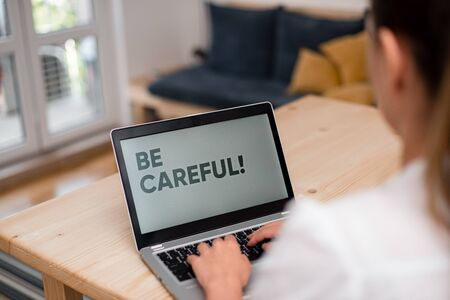 Conceptual hand writing showing Be Careful. Concept meaning making sure of avoiding potential danger mishap or harm woman with laptop smartphone and office supplies technology